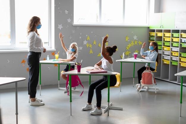 Crianças querendo responder a uma pergunta na aula