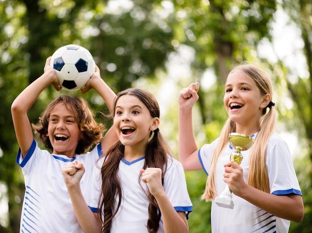 Crianças recebendo um troféu após vencer uma partida de futebol