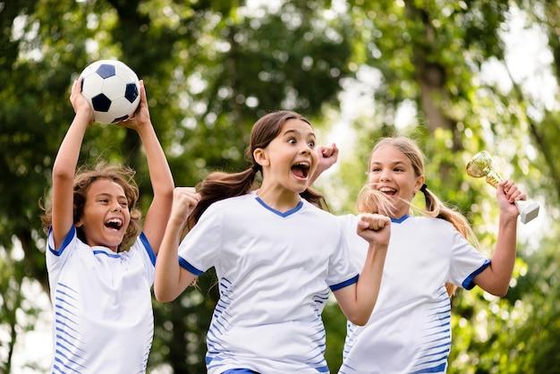Crianças recebendo um troféu depois de vencer uma partida de futebol ao ar livre