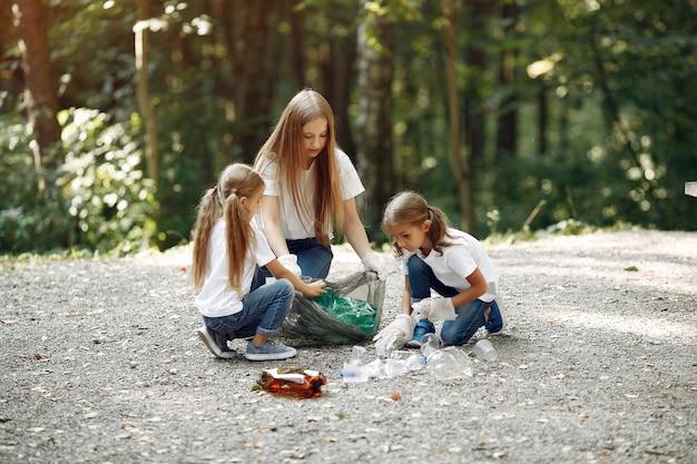 Crianças recolhe lixo em sacos de lixo no parque