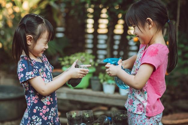 Crianças regando brotos de vegetais em uma garrafa reutilizada de plástico reciclado.