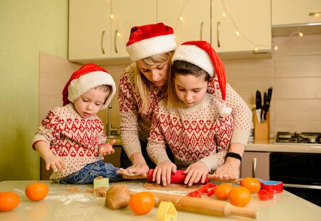 Crianças rindo e mãe cozinhando biscoitos de natal em casa. cozimento