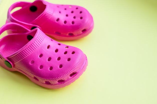 Crianças rosa flip-flop isolado em fundo amarelo. conceito de férias, relaxamento. copie o espaço. par de chinelos. sandálias de praia para crianças. conceito de viagens de verão.