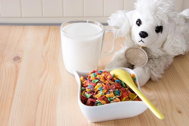 Crianças saudáveis café da manhã rápido. o cereal, o leite e o cão coloridos do arroz brincam no fundo de madeira. espaço da cópia