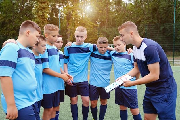 Crianças se abraçando e ouvindo a explicação do treinador com a prancheta nas mãos