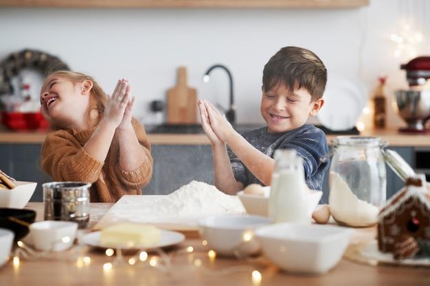 Crianças se agarrando com farinha enquanto assam biscoitos de natal