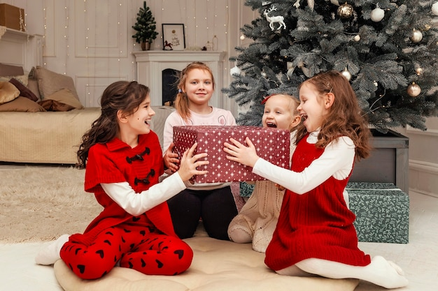 Crianças se alegram com o presente de ano novo sentadas no chão perto da árvore de natal