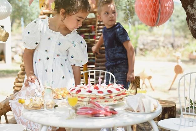 Crianças se arrumam para lanchar na mesa de aniversário