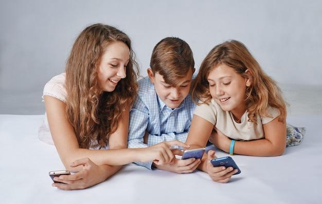 Crianças se concentram em brincar com smartphones