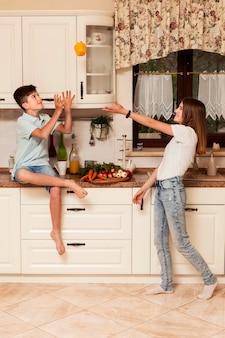 Crianças se divertindo com legumes na cozinha