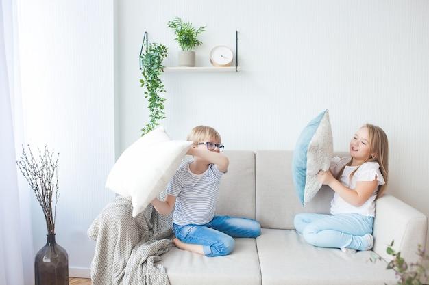 Crianças se divertindo dentro de casa. crianças brincando no sofá. luta de almofadas. irmão e irmã em casa fazendo bagunça.