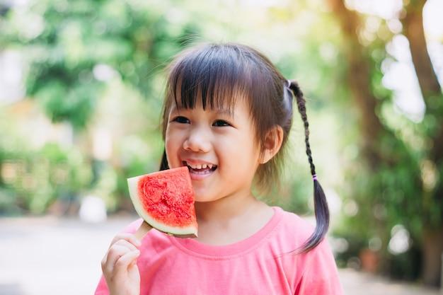 Crianças se divertindo e comemorando as férias de verão quente comendo melancia