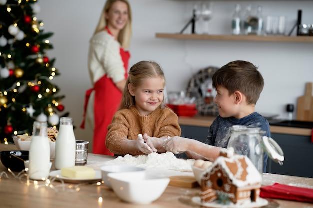 Crianças se divertindo muito enquanto assam biscoitos para o natal