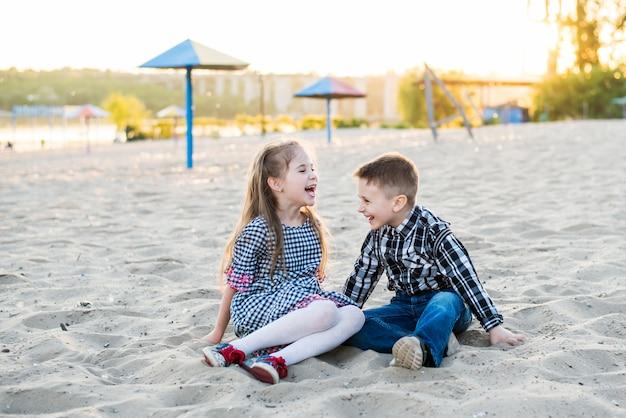 Crianças se divertindo na praia em dia quente de verão. menino e menina são lough