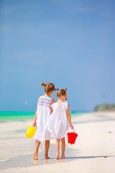 Crianças se divertindo na praia tropical, jogando juntos em águas rasas
