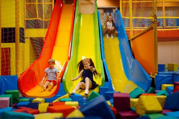 Crianças se divertindo no escorregador inflável, playground no centro de entretenimento.