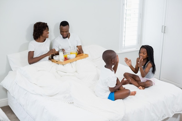 Crianças se divertindo no quarto enquanto os pais tomando café da manhã