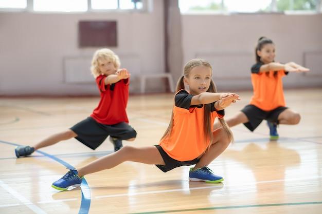 Crianças se exercitando na academia e parecendo concentradas