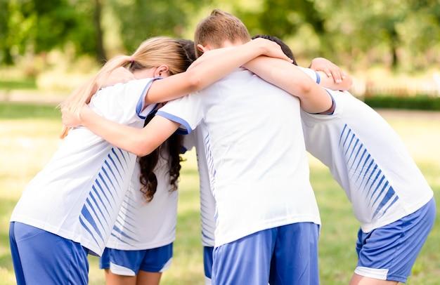Crianças se incentivando antes de uma partida de futebol