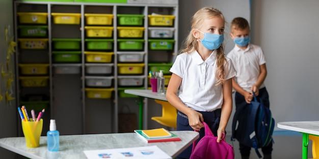 Crianças se preparando para sair da aula em época de pandemia