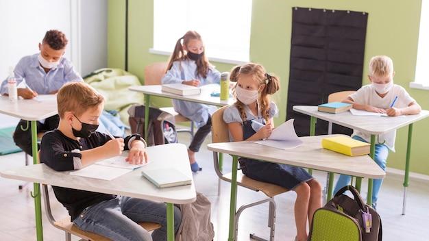 Crianças se protegendo com máscaras faciais na aula