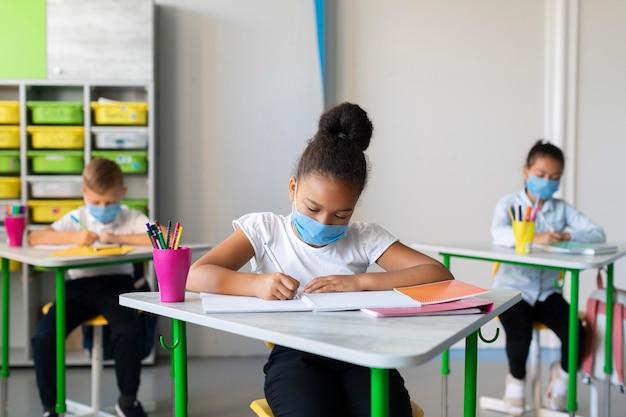 Crianças se protegendo com máscaras faciais na sala de aula