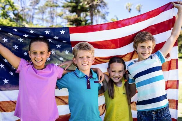 Crianças, segurando a bandeira americana no parque