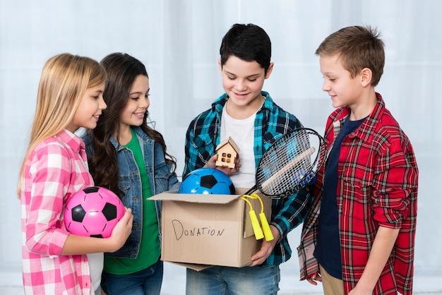 Crianças, segurando a caixa de doação
