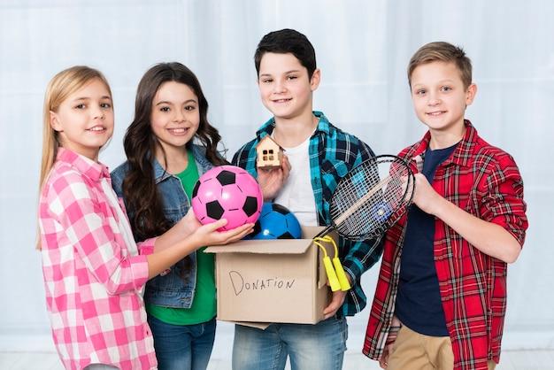 Crianças segurando a caixa de doações