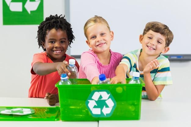 Crianças, segurando a garrafa reciclada na sala de aula