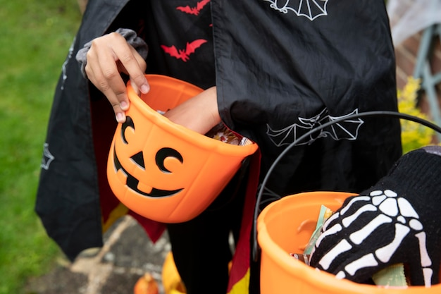 Crianças segurando baldes de doces ou travessuras