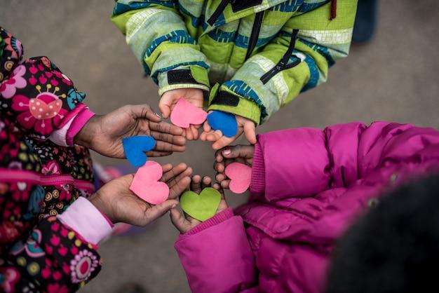 Crianças segurando corações nas mãos