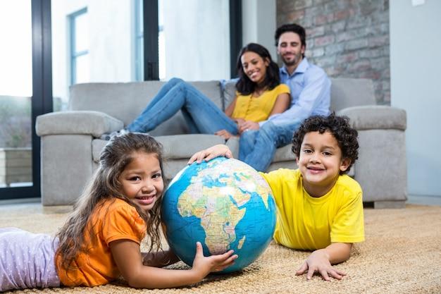 Crianças, segurando, globo, tapete, sala