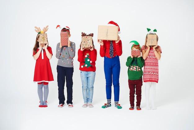 Crianças segurando um presente de natal na frente do rosto
