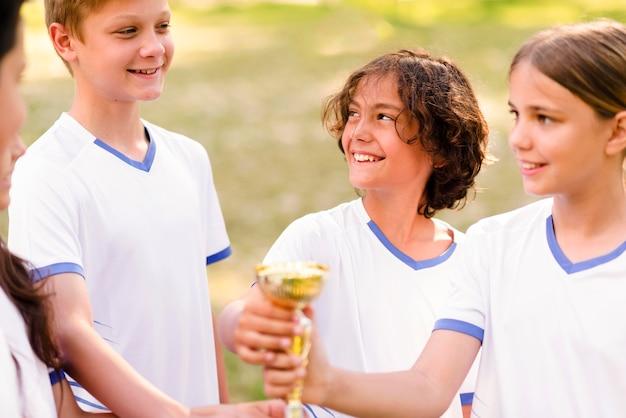 Crianças segurando um troféu de ouro