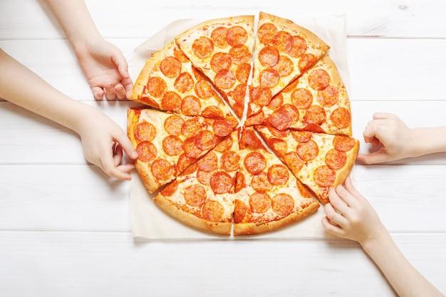 Crianças segurando uma fatia de pizza.
