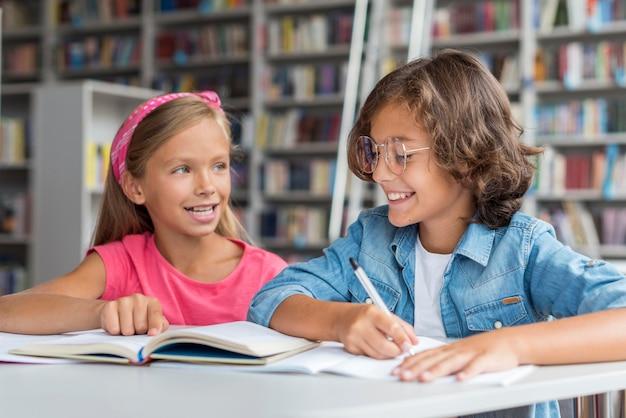Crianças sendo felizes enquanto fazem sua lição de casa