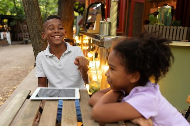 Crianças sentadas à mesa com tablet tiro médio
