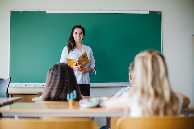 Crianças sentadas em sala de aula com professora