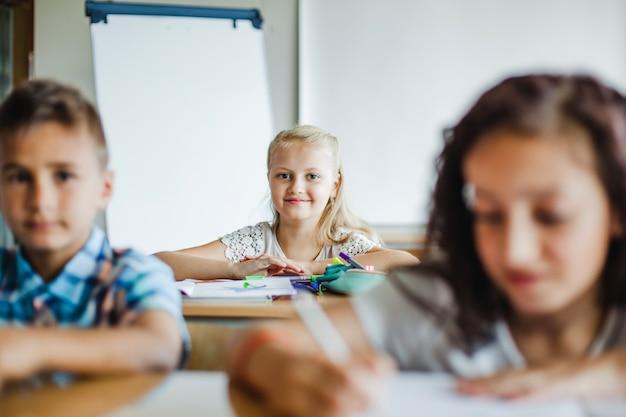 Crianças sentadas em sala de aula estudando