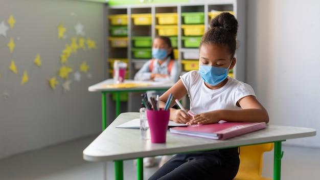 Crianças sentadas em suas mesas na aula