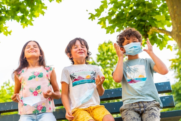 Crianças sentadas em um banco tirando suas máscaras cirúrgicas ao ar livre
