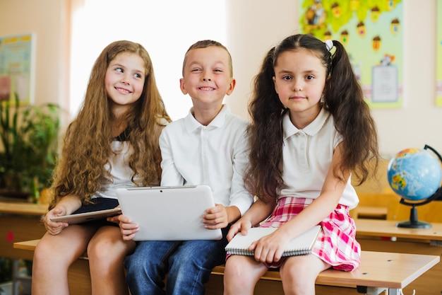 Crianças sentadas na mesa na sala de aula