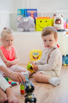 Crianças sentadas na sala de jogos no chão