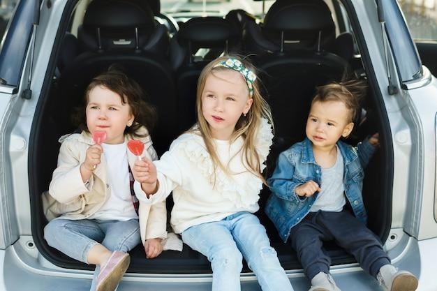 Crianças sentadas no porta-malas de um carro antes de uma viagem