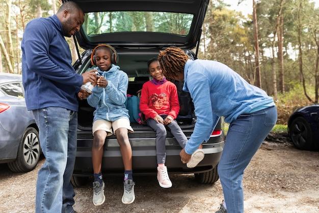 Crianças sentadas no porta-malas de um carro