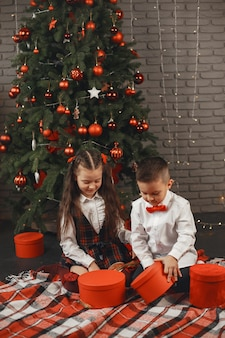Crianças sentadas perto da árvore de natal. as crianças abrem caixas com presentes.