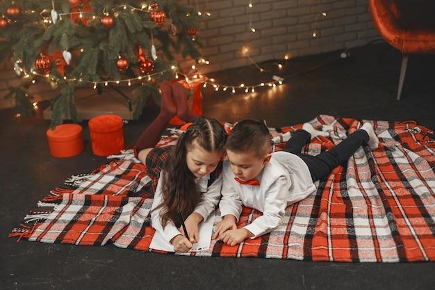 Crianças sentadas perto da árvore de natal. as crianças escrevem uma carta ao pai natal.