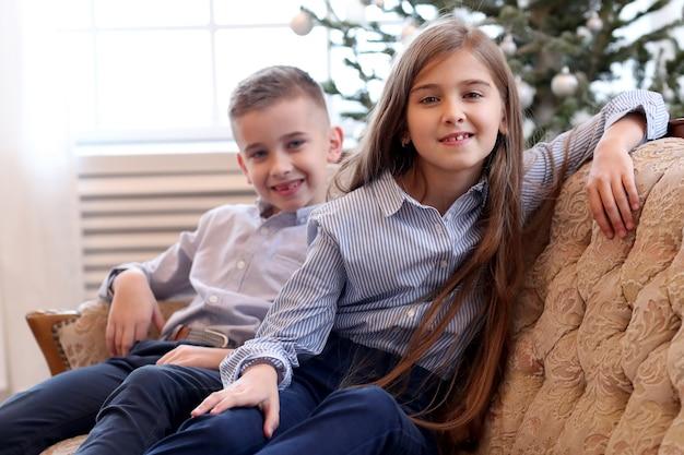Crianças sentam no sofá