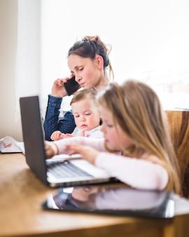 Crianças, sentando, ao lado, dela, mãe, falando telefone móvel